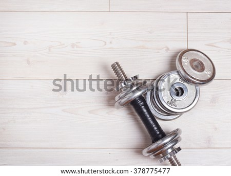 Top view of one silver dumbbell with extra weights on wooden floor. Workout and healthy lifestyle concept - stock photo