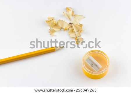 Top view of one yellow pencil, sharpener and shavings on white background - stock photo
