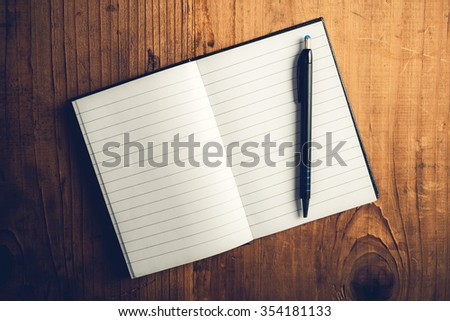Top view of open notebook with blank pages and pencil on old wooden desk, retro toned image as copy space - stock photo