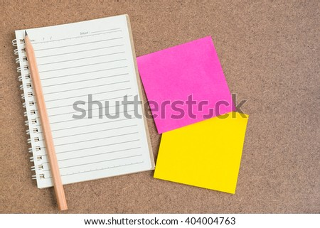 Top view of open spiral notebook, empty line paper with brown pencil and colorful sticky notes - notebook paper on brown background - stock photo