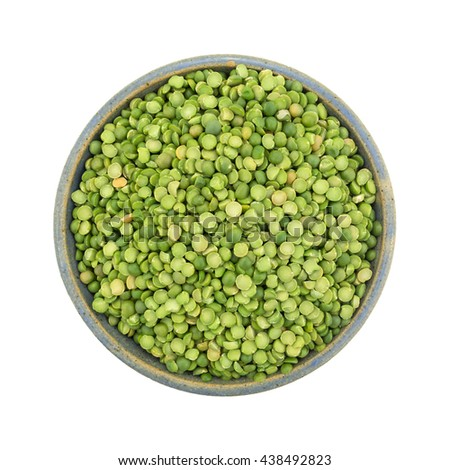 Top view of organic green split peas filling an old stoneware bowl isolated on a white background. - stock photo