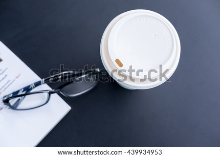 Top view of paper cup hot coffee with book and glasses on black table in coffee shop (selective focus) - stock photo