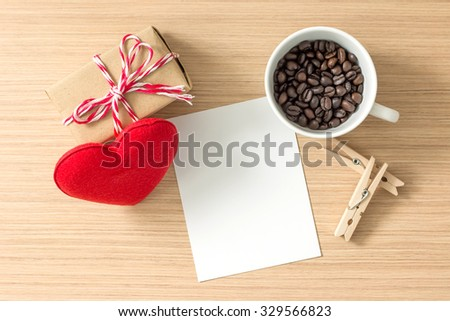 Top view of paper or cardboard, clothes pegs, red heart, gift box and coffee bean in coffee cup on wooden background. Lots of copy space for your idea. - stock photo