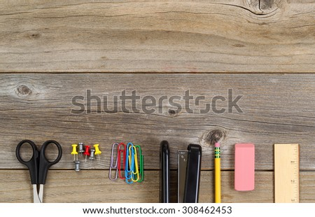 Top view of partial business and education supplies on rustic wood. - stock photo