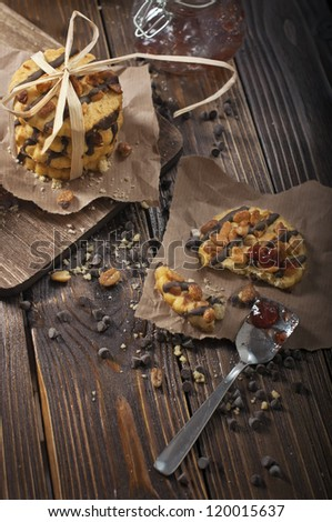 Top view of peanut biscuits, chocolate drops and jars with jam made in the dark tonality - stock photo