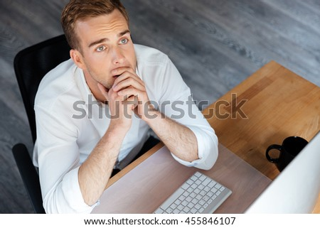 Top view of pensive young businessman working with computer and thinking at workplace - stock photo