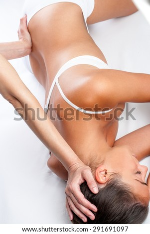 Top view of physiotherapist doing visceral spine treatment on woman. - stock photo