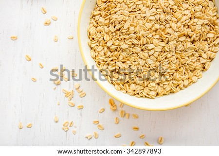 top view of pile of oatmeal flakes in a bowl on white table with copy space - stock photo