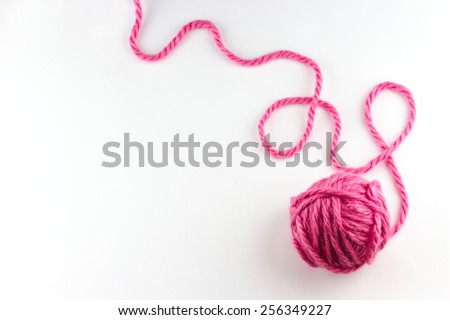 Top view of pink yarn ball with woolen thread on white background  - stock photo