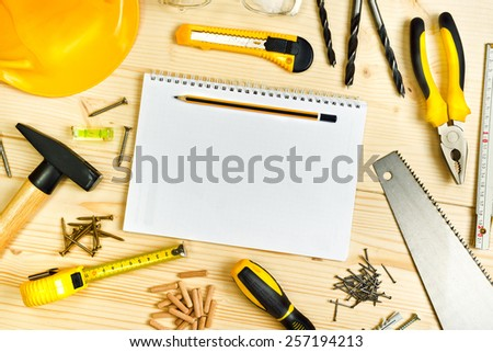 Top View of Planning a Project in Carpentry and Woodwork Industry, Notebook and Assorted Woodwork and Carpentry Tools  on Pinewood Workshop Table. - stock photo
