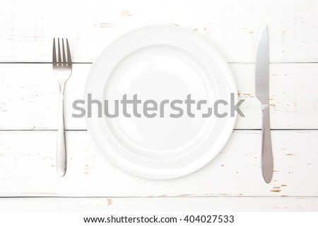 Top view of plate, fork and knife on wooden background - stock photo
