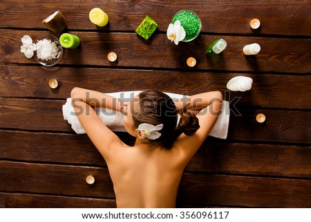 Top view of pretty woman laying in spa salon with closed eyes and relaxed - stock photo