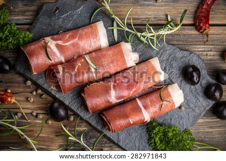 Top view of prosciutto on rustic background - stock photo