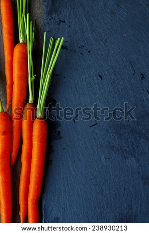 Top view of raw carrots with green leaves over wooden background. Copy space. Vegetable. Food - stock photo