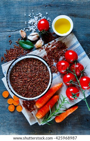 Top view of raw red rice and fresh vegetables ingredients for tasty cooking on rustic wooden background.  Healthy eating or vegetarian concept. - stock photo