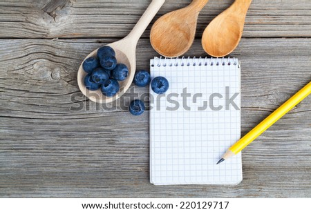 top view of recipe book with fresh Blueberries ingredients on wooden table - stock photo