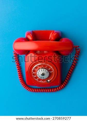 top view of red vintage phone on blue background - stock photo