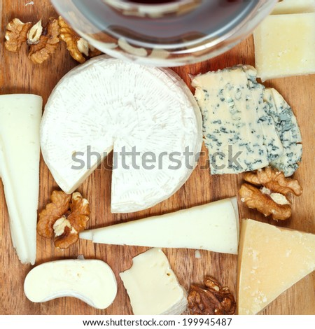 top view of red wine glass and assorted cheeses on wooden plate close up - stock photo