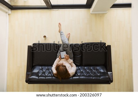 Top view of relaxed young lady sitting on a sofa working on a digital tablet. Aerial view of female sitting on couch using tablet computer. - stock photo