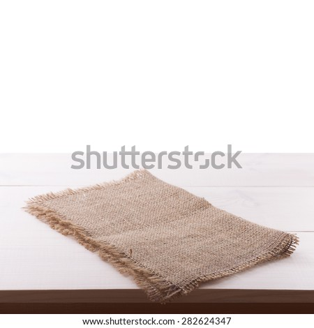 Top view of rough burlap napkin tablecloth on white wooden table isolated. Flat mock up for design. - stock photo