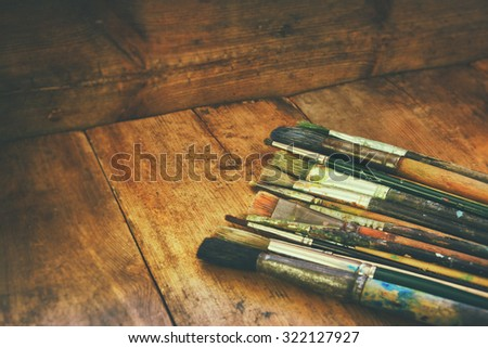 top view of set of used paint brushes and palette over wooden table  - stock photo