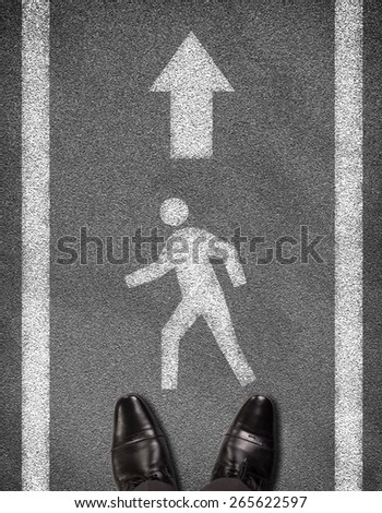Top view of shoes standing on asphalt road with two line and pedestrian sign. Business concept - stock photo