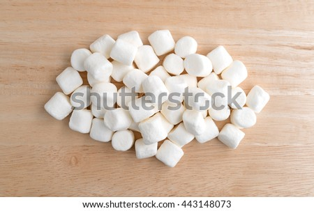 Top view of small bite size marshmallows on a wood cutting board illuminated with natural light. - stock photo