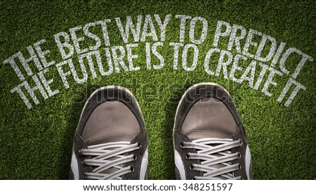 Top View of Sneakers on the grass with the text: The Best Way to Predict the Future is to Create It - stock photo