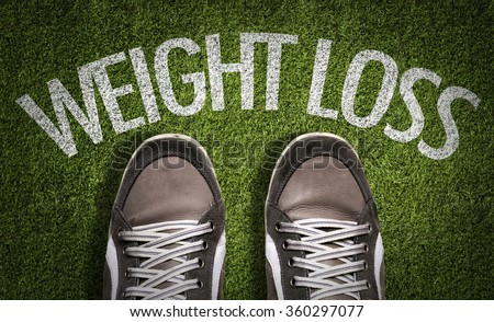 Top View of Sneakers on the grass with the text: Weight Loss - stock photo