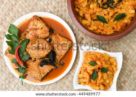 Top view of spicy and hot king fish curry with cooked tapioca / cassava root Kerala India. Barracuda Fish curry with green chili, green curry leaf, coconut milk and mango Asian cuisine. - stock photo
