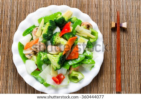 Top view of steamed mixed vegetables in large plate with bamboo mat underneath.  - stock photo
