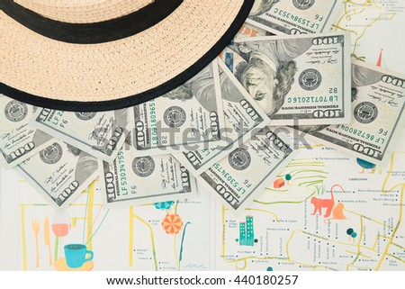 Top view of straw hat and money on the map - stock photo
