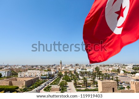 Top view of streets at Monastir city, Tunisia  Minaret of mosque and Ribat as a fortress  Red Tunisian flag - stock photo