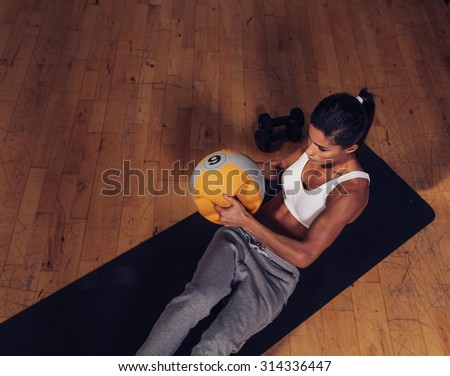 Top view of strong young woman doing core workout using kettlebell weight. Muscular female exercising on fitness mat in gym. - stock photo
