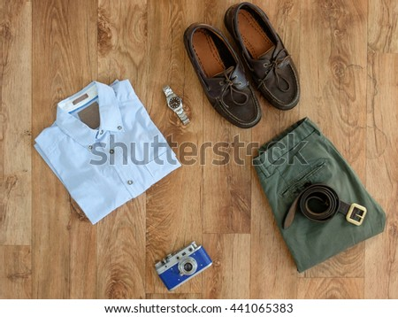 Top view of stylish clothes isolated on wooden background - stock photo