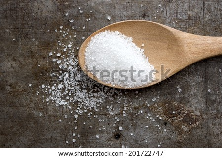 Top view of sugar in a wooden spoon on rustic table - stock photo