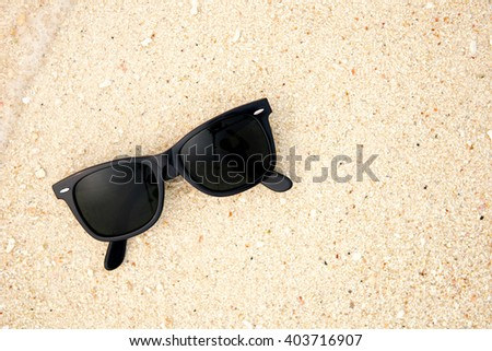 Top view of sunglasses on the beach near the blue sea. Sand and glasses. Summer vacation actually relaxing, Thailand. Close up. - stock photo