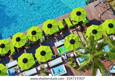 Top view of swimming pool side with a seat and umbrella - stock photo