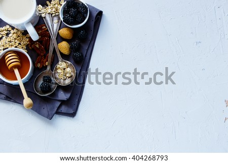 Top view of tasty breakfast background with oat flakes, honey, berries and nuts on white vintage kitchen table, place for text, border. Healthy food, Diet, Detox, Clean Eating or Vegetarian concept. - stock photo