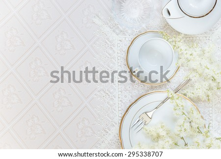 Top view of the beautifully decorated table with white plates, crystal glasses, linen napkin, cutlery and flowers on luxurious tablecloths, with space for text - stock photo