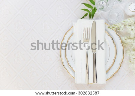 Top view of the beautifully decorated table with white plates, crystal glasses, linen napkin, cutlery and white flower on luxurious tablecloths, with space for text - stock photo