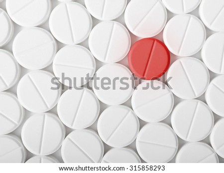 Top view of the heap of white medicine pills on white surface. One red medicine tablet is as a concept of a vaccine. - stock photo