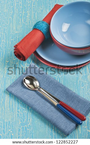 Top view of the kitchen utensils: red and blue plates, spoons and napkins on a blue cracked background - stock photo