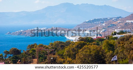 Top view of the sea, green trees and Mykonos port with cruise ship. - stock photo