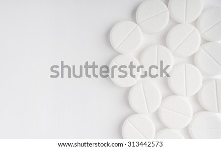 Top view of the Spilled white pills on the white surface - stock photo