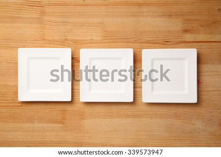 top view of the square saucer on the wooden background - stock photo