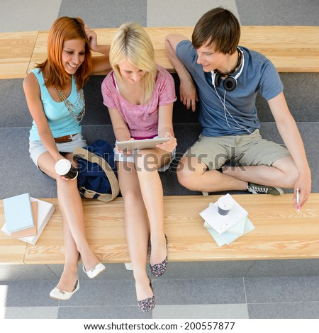 Top view of three college students looking at tablet sitting - stock photo