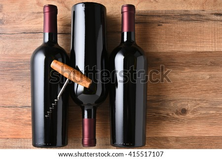 Top view of three red wine bottles on a wood table with an old fashioned corkscrew. - stock photo