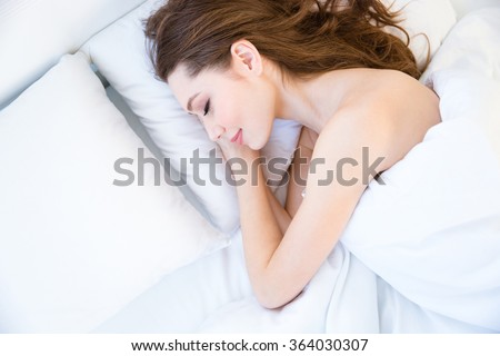 Top view of tired beautiful young woman with long hair sleeping on bed in bedroom - stock photo