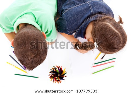 Top view of two children drawing with colorful crayons, isolated over white - stock photo